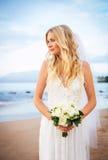 Belle jeune mariée dans la robe de mariage avec des fleurs au coucher du soleil sur le beaut Photos stock
