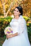 Belle jeune mariée dans le jour du mariage sur le fond de la forêt d'automne avec un beau bouquet Images libres de droits