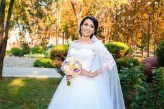 Belle jeune mariée dans le jour du mariage sur le fond de la forêt d'automne avec un beau bouquet Photos libres de droits