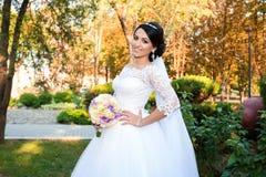 Belle jeune mariée dans le jour du mariage sur le fond de la forêt d'automne avec un beau bouquet Photographie stock libre de droits