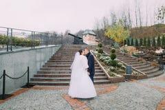 Belle jeune mariée dans le long baiser blanc de part de robe avec le marié élégant sur des escaliers dehors Vieux canon au fond Photographie stock