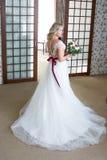 Belle jeune mariée dans le voile qui développe des prises un bouquet dans des ses mains image libre de droits