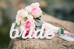 Belle jeune mariée de bouquet et de mot sur la roche Concept de mariage de plage Photographie stock