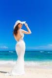 Belle jeune mariée de brune dans la robe de mariage et le chapeau de paille blancs ha Photographie stock libre de droits