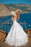 Belle jeune mariée de sourire dans la robe de mariage avec le bouquet des fleurs Photographie stock libre de droits