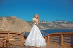 Belle jeune mariée de sourire dans la robe de mariage avec le bouquet des fleurs Photographie stock