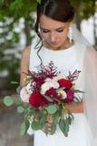 Belle jeune mariée dehors avec un bouquet Image stock