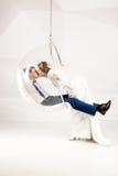 Belle jeune mariée embrassant le marié s'asseyant dans la chaise de bulle au studio Images stock