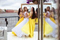 Belle jeune mariée et deux demoiselles d'honneur ensemble sur une terrasse d'été un restaurant de mer Images stock