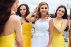 Belle jeune mariée et deux demoiselles d'honneur ensemble sur une terrasse d'été un restaurant de mer Photos stock