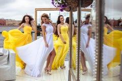 Belle jeune mariée et deux demoiselles d'honneur ensemble sur une terrasse d'été un restaurant de mer Photos libres de droits