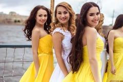 Belle jeune mariée et deux demoiselles d'honneur ensemble sur une terrasse d'été un restaurant de mer Photographie stock