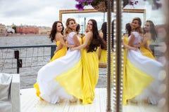 Belle jeune mariée et deux demoiselles d'honneur ensemble sur une terrasse d'été un restaurant de mer Image libre de droits