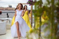Belle jeune mariée et deux demoiselles d'honneur ensemble sur une terrasse d'été un restaurant de mer Images libres de droits
