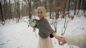Belle jeune mariée et suivre son marié dans la forêt d'hiver clips vidéos