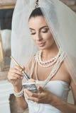 Belle jeune mariée faisant le maquillage Photographie stock libre de droits
