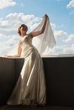 Belle jeune mariée heureuse avec le tissu de vol au-dessus du ciel Photographie stock