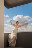 Belle jeune mariée heureuse avec le tissu de vol au-dessus du ciel Photos stock