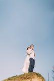 Belle jeune mariée heureuse embrassant de retour son marié au sommet de la colline contre au ciel Photo libre de droits