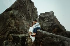Belle jeune mariée heureuse et marié élégant élégant étreignant sur la roche photo libre de droits
