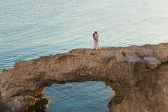 Belle jeune mariée magnifique et marié élégant sur des roches, sur le fond d'une mer, cérémonie de mariage sur la Chypre image libre de droits