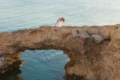 Belle jeune mariée magnifique et marié élégant sur des roches, sur le fond d'une mer, cérémonie de mariage sur la Chypre images libres de droits
