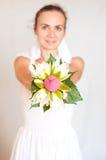 Belle jeune mariée montrant son bouquet Image libre de droits