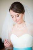 Belle jeune mariée obtenant habillée le jour du mariage Photo stock