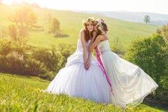 2 belle jeune mariée pendant le matin, le pré idyllique, symbole d'amitié Photographie stock libre de droits
