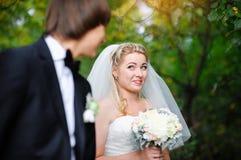 Belle jeune mariée regardant au-dessus de son épaule et sourire Photo libre de droits