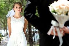 Belle jeune mariée regardant son marié cachant un bouquet Images libres de droits