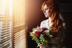 Belle jeune mariée rouge de cheveux près de fenêtre Photographie stock