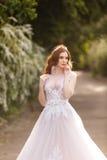 Belle jeune mariée rousse dans la robe de mariage fantastique dans le jardin de floraison Photographie stock