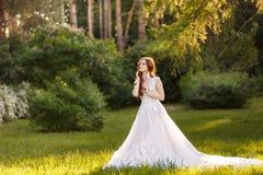 Belle jeune mariée rousse dans la robe de mariage fantastique dans le jardin de floraison Images stock