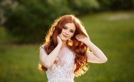 Belle jeune mariée rousse dans la robe de mariage fantastique dans le jardin de floraison Photographie stock libre de droits