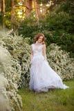 Belle jeune mariée rousse dans la robe de mariage fantastique dans le jardin de floraison Image libre de droits