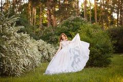 Belle jeune mariée rousse dans la robe de mariage fantastique dans le jardin de floraison Photos stock