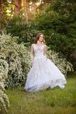 Belle jeune mariée rousse dans la robe de mariage fantastique dans le jardin de floraison Photo libre de droits