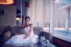 Belle jeune mariée s'asseyant à un café d'intérieur Images stock