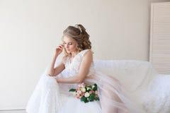 Belle jeune mariée s'asseyant sur un divan blanc dans la lingerie Photos libres de droits