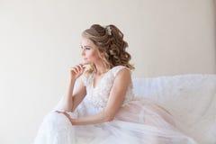 Belle jeune mariée s'asseyant sur un divan blanc dans la lingerie Image stock