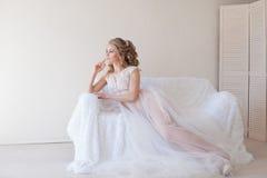 Belle jeune mariée s'asseyant sur un divan blanc dans la lingerie Images stock