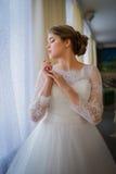 Belle jeune mariée tenant la fenêtre proche photos libres de droits