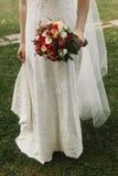 Belle jeune mariée tenant le bouquet de mariage, jeune mariée élégante dans la dentelle W Photos stock