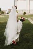 Belle jeune mariée tenant le bouquet de mariage, jeune mariée élégante dans la dentelle W Photo libre de droits