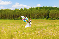 Belle jeune mariée tenant le groupe de ballons en parc Couples des jeunes mariés avec des ballons Nouveaux mariés avec des ballon Photographie stock libre de droits