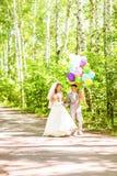 Belle jeune mariée tenant le groupe de ballons en parc Couples des jeunes mariés avec des ballons Nouveaux mariés avec des ballon Photos libres de droits