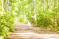 Belle jeune mariée tenant le groupe de ballons en parc Couples des jeunes mariés avec des ballons Nouveaux mariés avec des ballon Images libres de droits