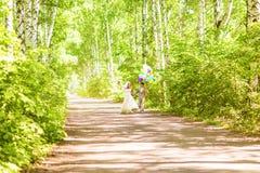 Belle jeune mariée tenant le groupe de ballons en parc Couples des jeunes mariés avec des ballons Nouveaux mariés avec des ballon Image stock