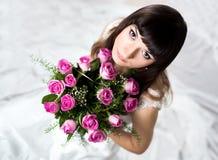 Belle jeune mariée tenant un bouquet des fleurs roses Photos libres de droits